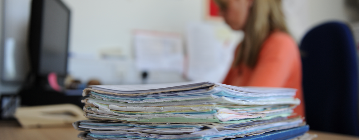A stack of paper medical records on desk